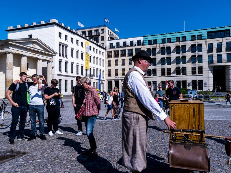 A traditional Organ Grinder by the Brandenburg Gate is Berlin`s most famous landmark. stock photos