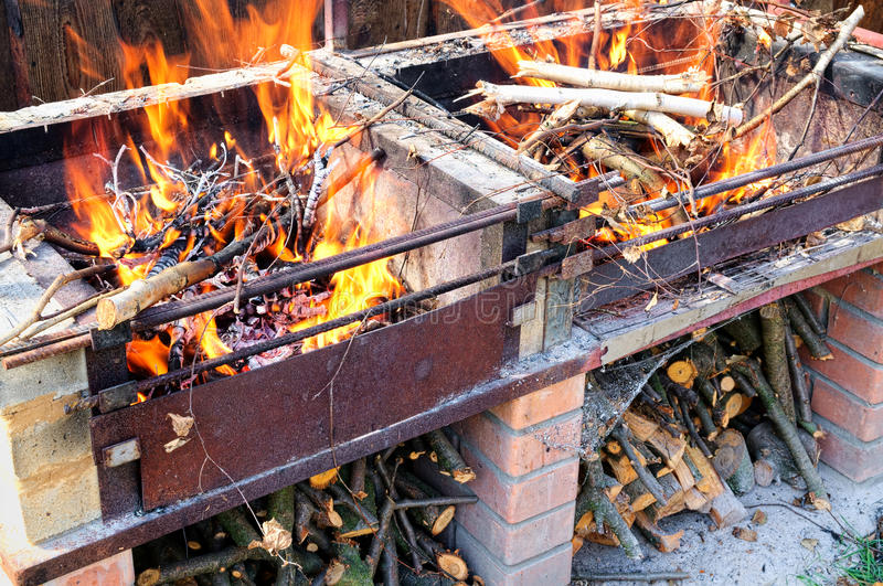 Brandend brandhout in zelf gemaakt baksteen en metaal stock foto