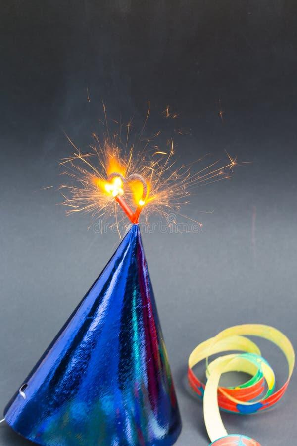 Brandend hart op partijhoeden, zwarte achtergrond, verjaardagskaart royalty-vrije stock fotografie