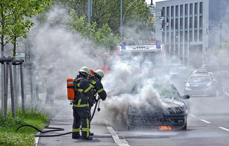 Brandend motorvoertuig uit gezet door brandweerlieden in beschermende klonter stock afbeeldingen