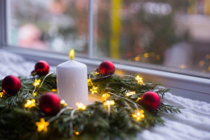 Brandend witte die kaars in sparkroon met rode die Kerstmisballen wordt verfraaid en met gloeiende slinger met warm licht op witt stock fotografie