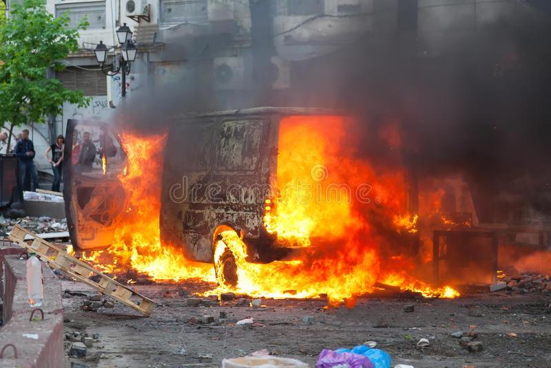 Brandende auto in het centrum van stad tijdens onrust stock afbeelding