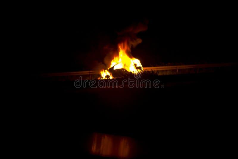 Brandende auto op de weg in de nacht royalty-vrije stock foto's