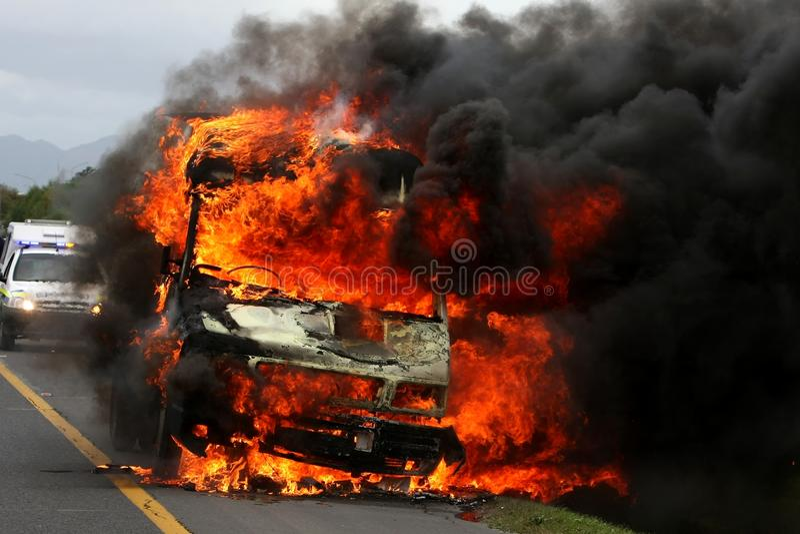 Brandende Bestelwagen met Politiewagen op Achtergrond