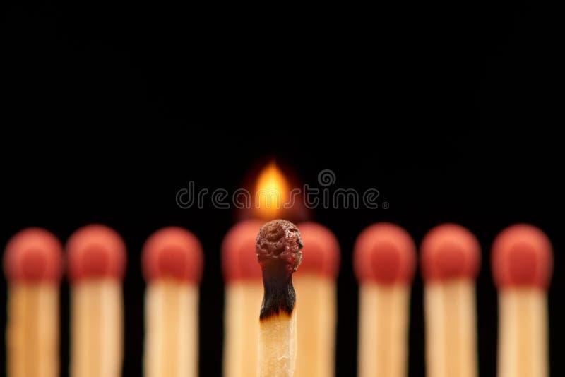 Brandende gelijke die zich voor acht rode houten gelijken bevinden stock afbeeldingen