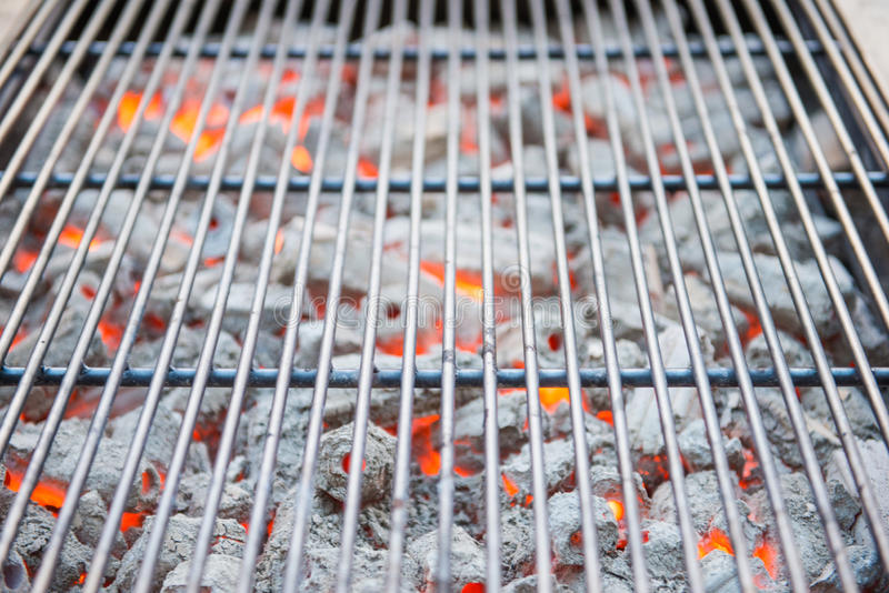 Brandende houtskool met grillplaat voor BBQ stock afbeeldingen
