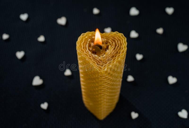 Brandende kaars in de vorm van hart op een donkere achtergrond met witte harten stock foto's