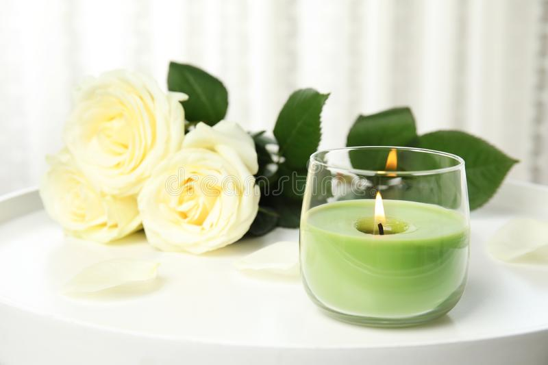Brandende kaars in glashouder en rozen op witte lijst royalty-vrije stock foto