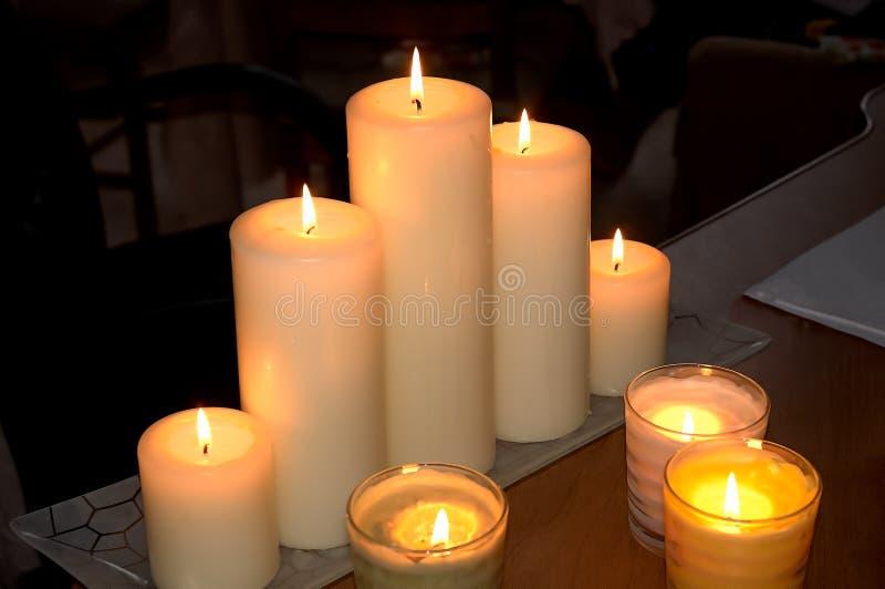Brandende kaarsen op een houten lijst tegen een donkere ruimteachtergrond royalty-vrije stock fotografie