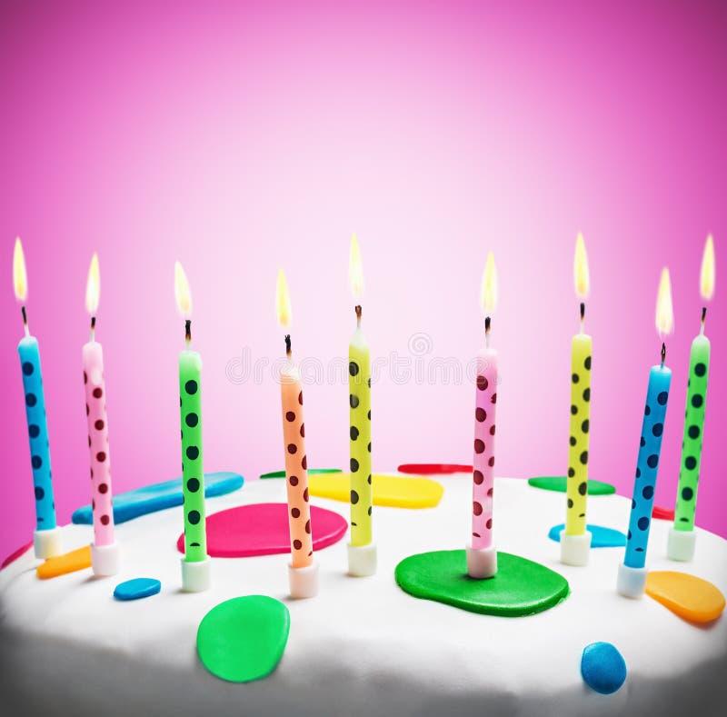 Brandende kaarsen op een verjaardagscake royalty-vrije stock afbeeldingen