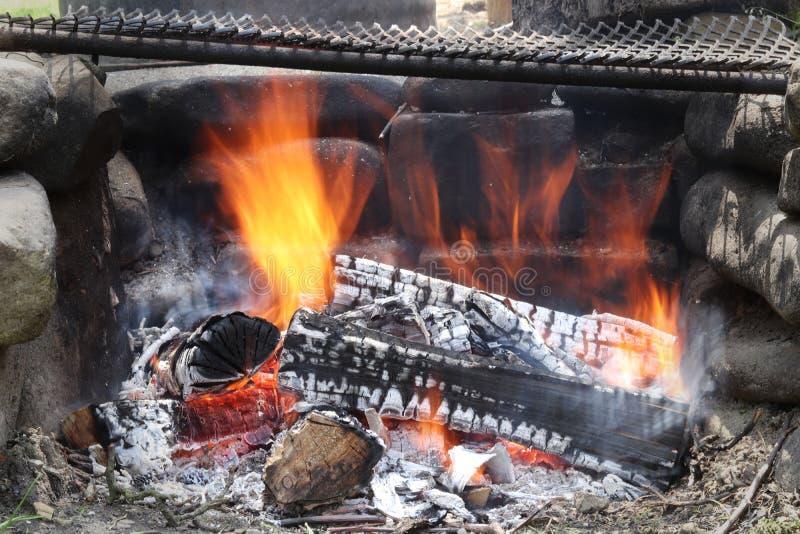 Brandende logboeken die in een barbecuebrand vlammen Eigengemaakte kampbrand met zwart voetbalveld Openluchtlevensstijl en natuur stock afbeeldingen