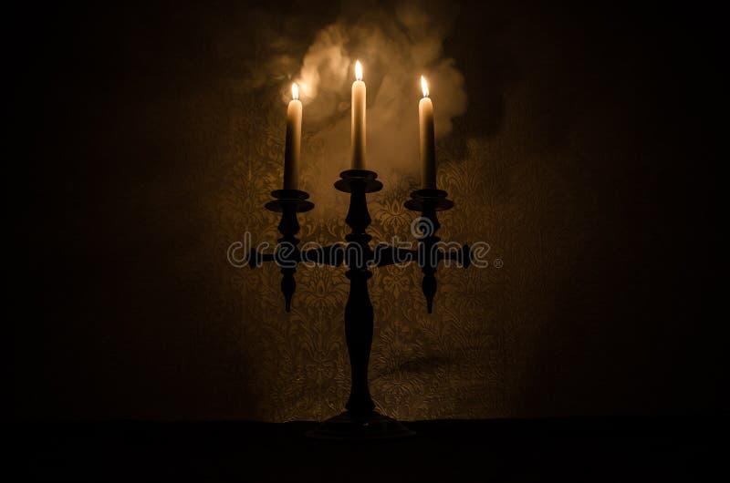 Brandende oude kaars uitstekende houten kandelaar op donkere gestemde mistige Achtergrond stock fotografie