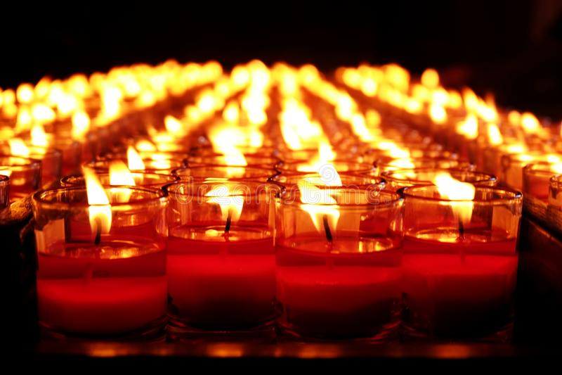 Brandende rode kaarsen Kaarsen lichte achtergrond Kaarsvlam bij nacht stock fotografie