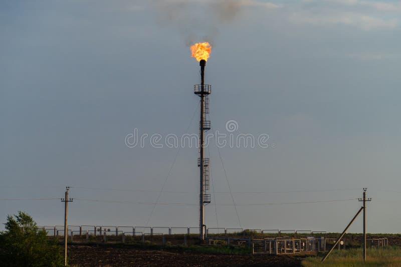 Brandende toorts bij de raffinaderij tegen de grijze hemel royalty-vrije stock afbeelding