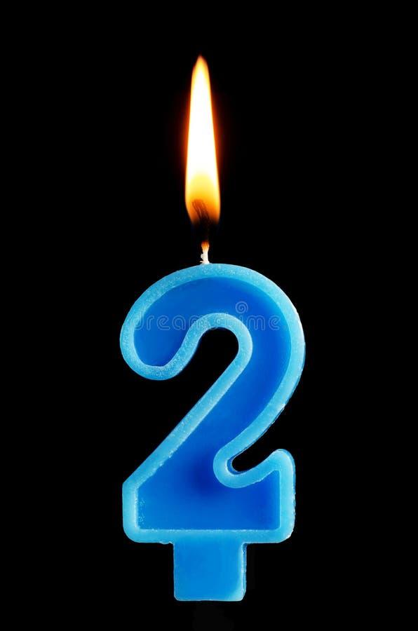 Brandende verjaardagskaars in de vorm van 2 twee die cijfers voor cake op zwarte achtergrond worden geïsoleerd Het concept het vi stock afbeelding