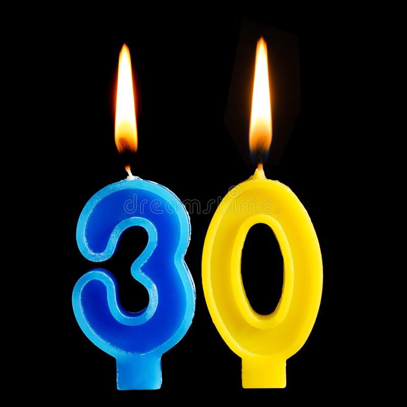 Brandende verjaardagskaarsen in de vorm van 30 dertig die cijfers voor cake op zwarte achtergrond worden geïsoleerd Het concept h stock foto