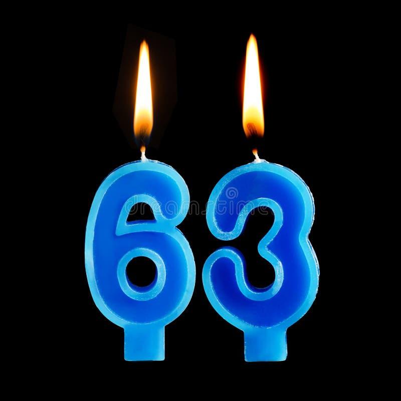 Brandende verjaardagskaarsen in de vorm van 63 die drieënzestig voor cake op zwarte achtergrond wordt geïsoleerd royalty-vrije stock afbeelding