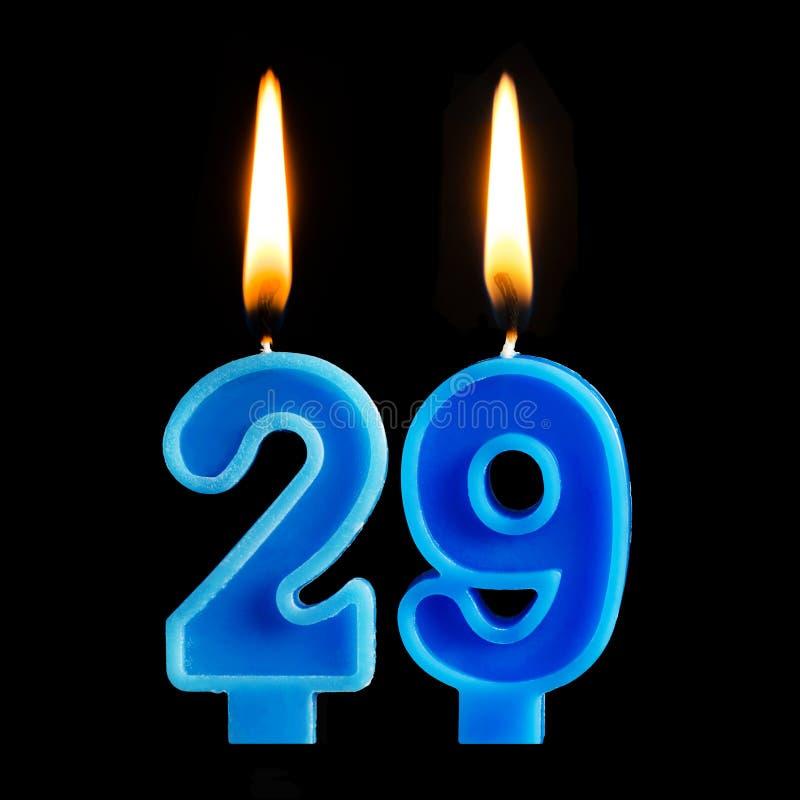 Brandende verjaardagskaarsen in de vorm van 29 die negenentwintig voor cake op zwarte achtergrond wordt geïsoleerd Het concept he royalty-vrije stock foto's