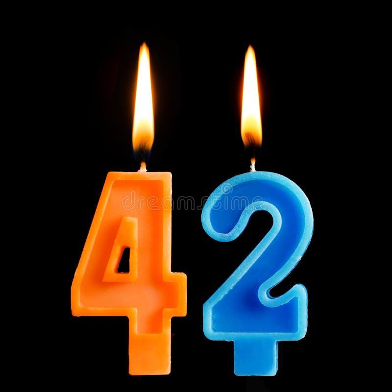 Brandende verjaardagskaarsen in de vorm van 42 die tweeënveertig voor cake op zwarte achtergrond wordt geïsoleerd stock afbeelding