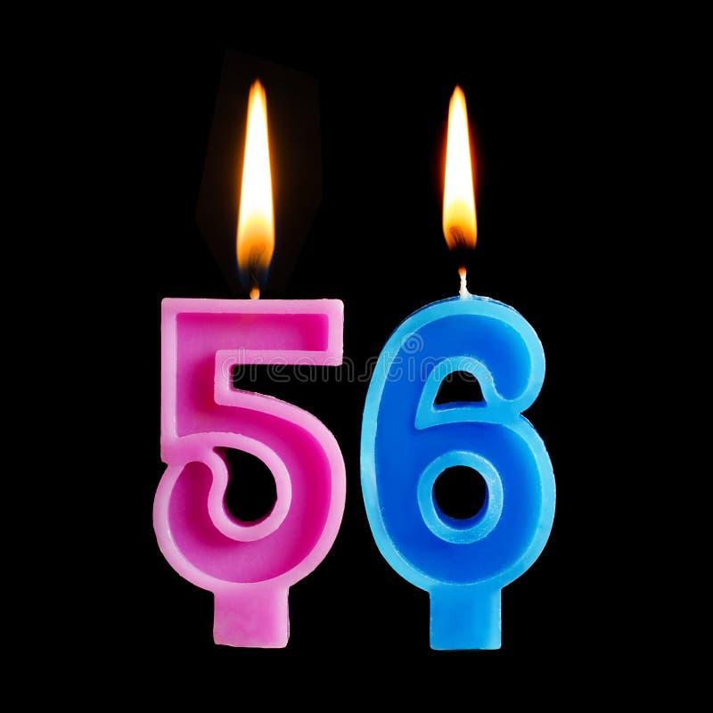 Brandende verjaardagskaarsen in de vorm van 56 die zesenvijftig voor cake op zwarte achtergrond wordt geïsoleerd royalty-vrije stock afbeelding