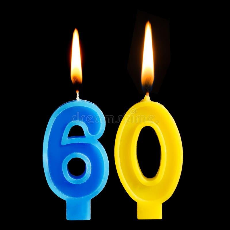 Brandende verjaardagskaarsen in de vorm van 60 zestig die cijfers voor cake op zwarte achtergrond worden geïsoleerd Het concept h stock afbeelding
