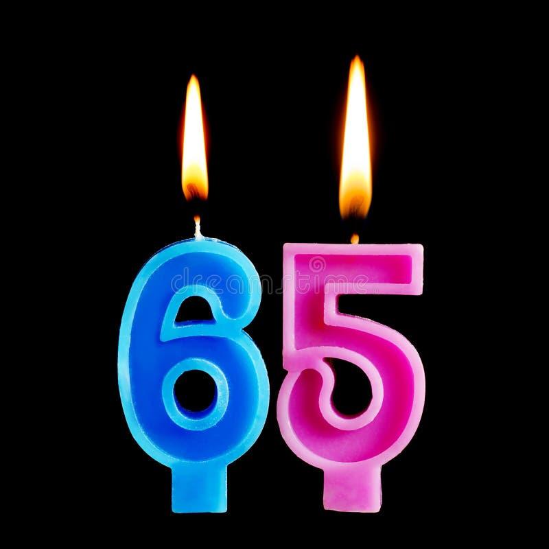 Brandende verjaardagskaarsen in de vorm van 65 zestig die ivecijfers voor cake op zwarte achtergrond worden geïsoleerd Het concep stock afbeeldingen