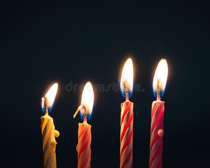 Brandende verjaardagskaarsen op donkere achtergrond met brand stock foto