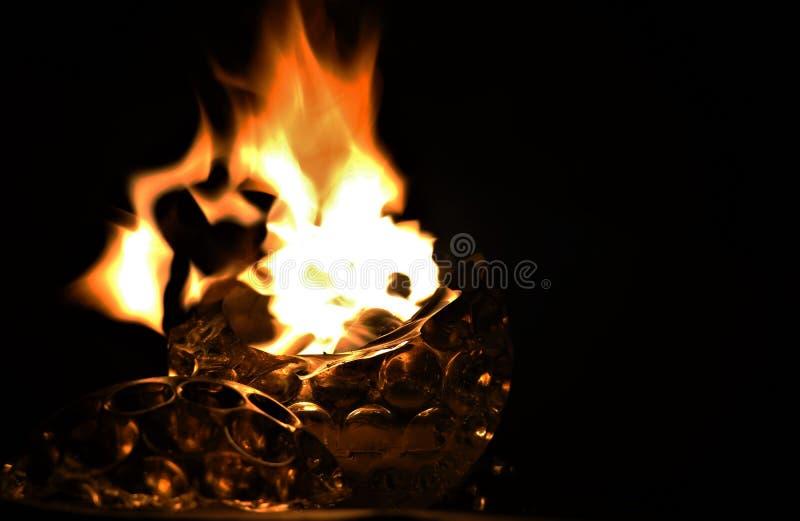 Brandflamma av den brutna exponeringsglasformstearinljuset i mörker royaltyfria bilder
