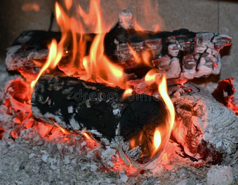 Brandflamma, brinnande trä på spisen Vedträt loggar in brandlampglaset, closeup arkivbilder