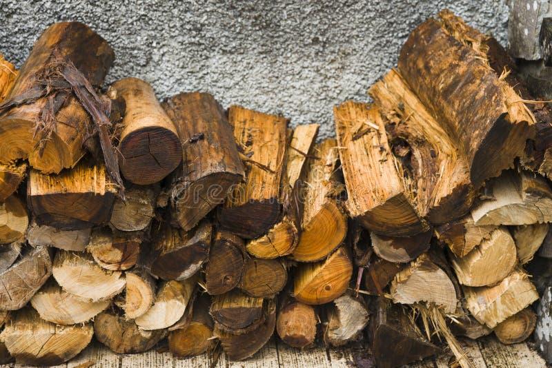 Brandhout dat in een stapel dichtbij de muur wordt gestapeld Het beeld is close-up stock fotografie