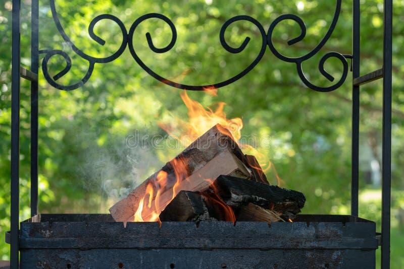 Brandhout en takken in de oude grill Het maken van een brand bij een picknick De mensen branden brandhout om steenkool te maken Z royalty-vrije stock foto