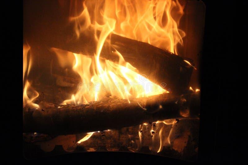 Brandhout het branden in de oven van een buitenhuis stock fotografie