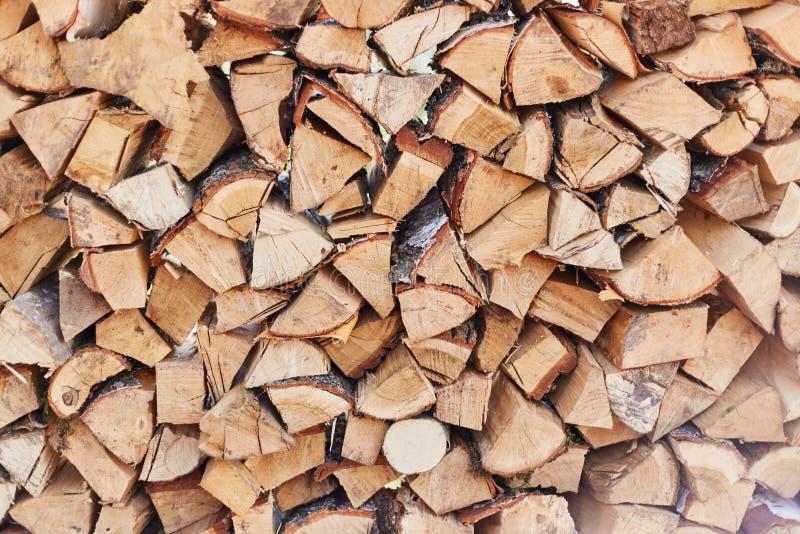 Brandhoutronde onder de muur wordt gestapeld die Een stapel van houten logboeken stock fotografie
