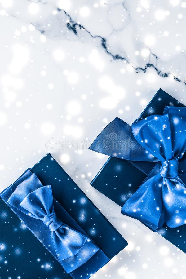 Winter holiday gift box with blue silk bow, snow glitter on marble background as Christmas and New Years presents for luxury. Branding, glamour and cold season royalty free stock images