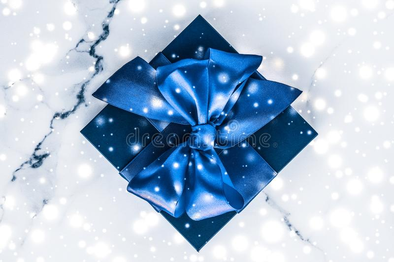 Winter holiday gift box with blue silk bow, snow glitter on marble background as Christmas and New Years presents for luxury. Branding, glamour and cold season royalty free stock photography