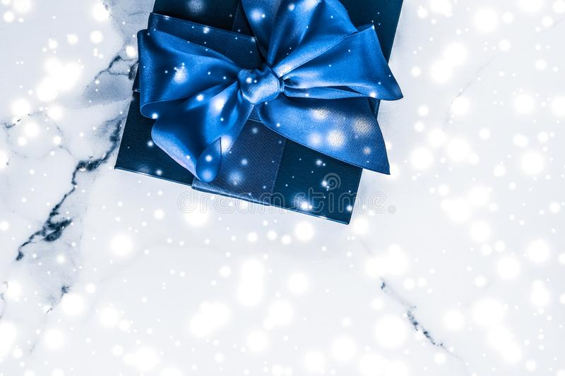 Winter holiday gift box with blue silk bow, snow glitter on marble background as Christmas and New Years presents for luxury. Branding, glamour and cold season stock images