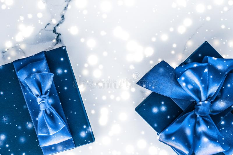 Winter holiday gift box with blue silk bow, snow glitter on marble background as Christmas and New Years presents for luxury. Branding, glamour and cold season stock photography