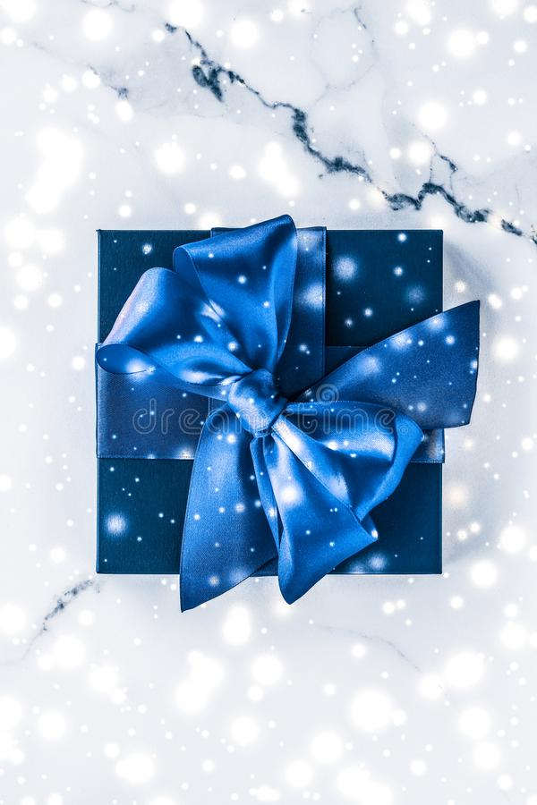 Winter holiday gift box with blue silk bow, snow glitter on marble background as Christmas and New Years presents for luxury. Branding, glamour and cold season stock image