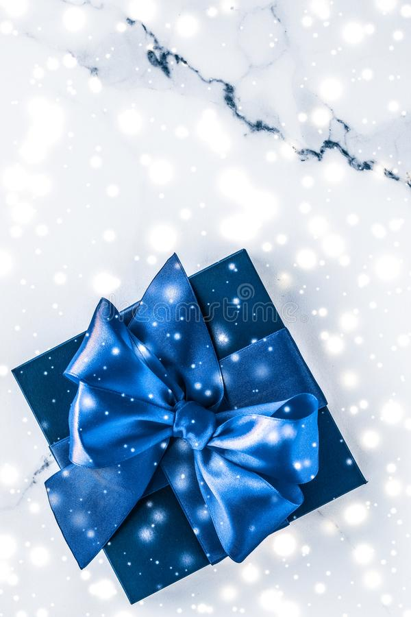 Winter holiday gift box with blue silk bow, snow glitter on marble background as Christmas and New Years presents for luxury. Branding, glamour and cold season royalty free stock photo