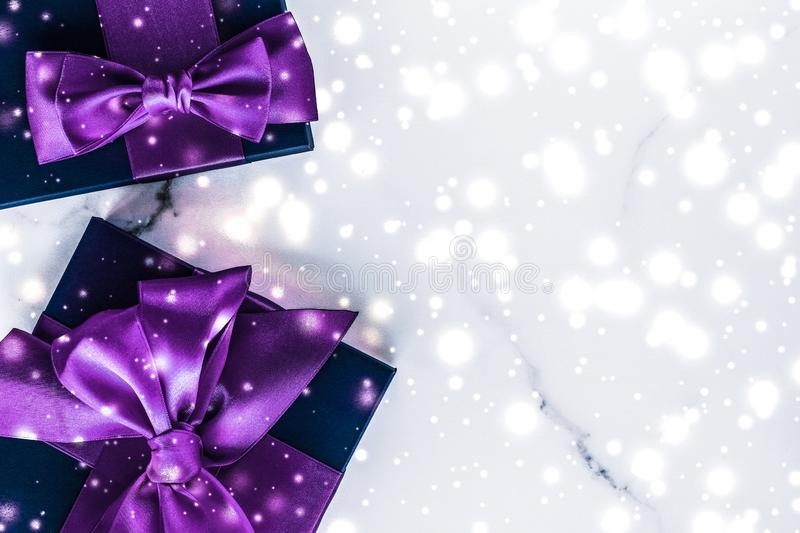 Winter holiday gift box with purple silk bow, snow glitter on marble background as Christmas and New Years presents for luxury. Branding, glamour and cold season royalty free stock photo