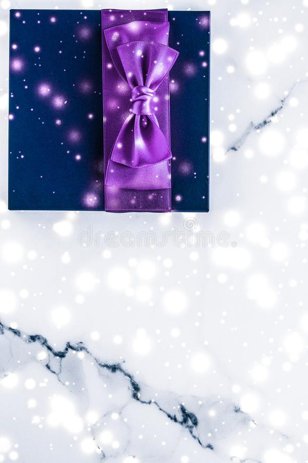 Winter holiday gift box with purple silk bow, snow glitter on marble background as Christmas and New Years presents for luxury. Branding, glamour and cold season royalty free stock image