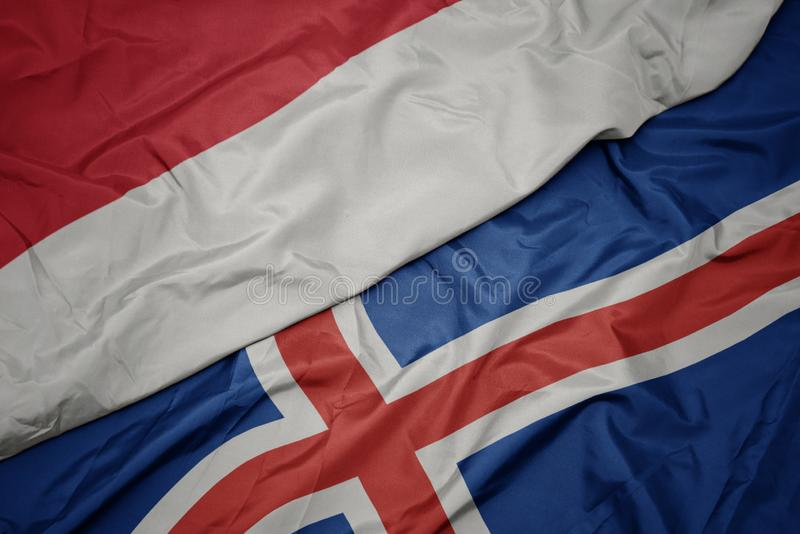 brandissant le drapeau coloré de l' islande et du drapeau national de l' indonésie photo stock