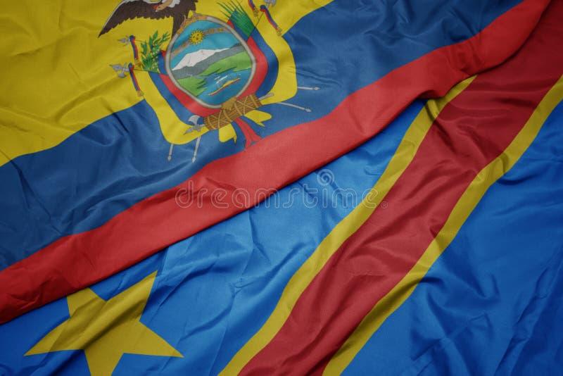 brandissant le drapeau coloré de la république démocratique du congo et du drapeau national de l' équateur image stock