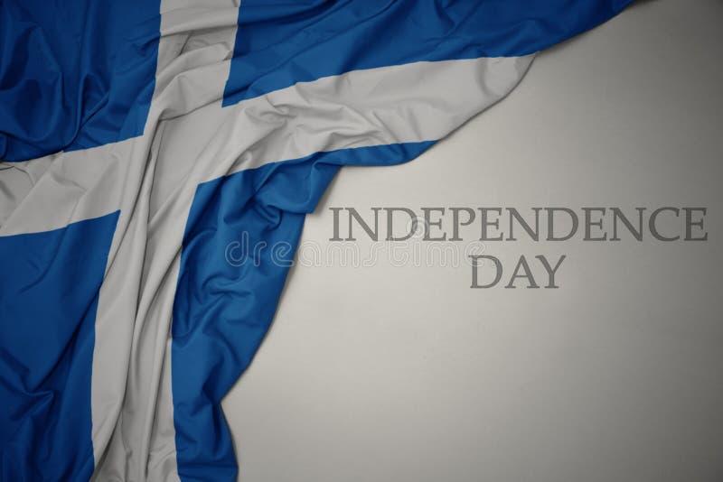 brandissant le drapeau national coloré de l' écosse sur fond gris avec le texte de la fête de l' indépendance photo libre de droits