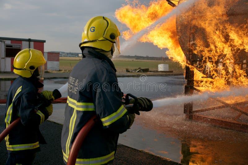 Brandkämpar som slåss brand arkivbilder