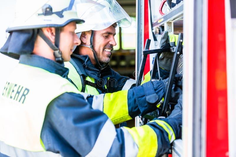 Brandkämpe som kontrollerar slangarna på brandmotorn arkivbild