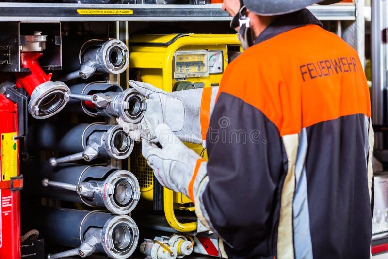 Brandkämpe som kontrollerar slangarna på brandmotorn fotografering för bildbyråer