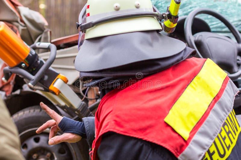 Brandkämpen arbetar med yrkesmässiga hjälpmedel på en kraschad bil arkivbilder