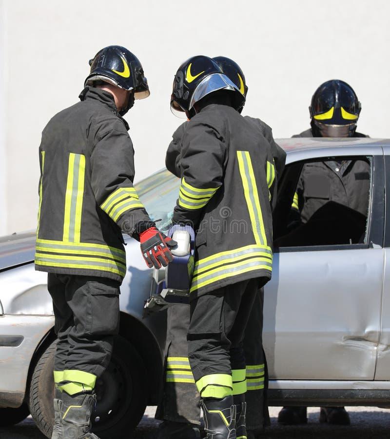 brandkåren öppnar dörren av bilen med en kraftig sax aft arkivfoto