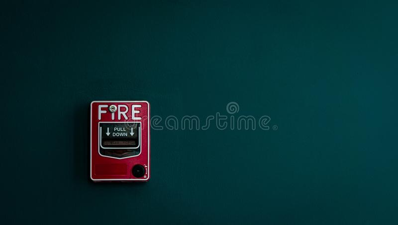 Brandlarm på mörker - grön betongvägg Varna och säkerhetssystem Nöd- utrustning för säkerhetsvarning Röd ask av brandlarmet royaltyfria foton
